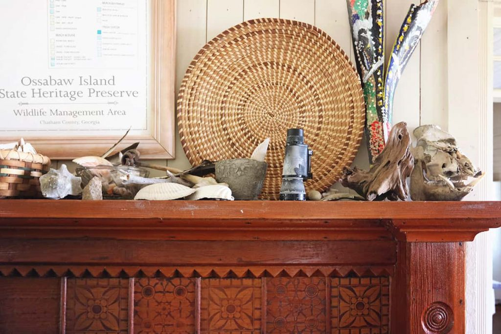 Beautiful carved wooden bookshelf with a woven grass basket and seashells perched on the mantel