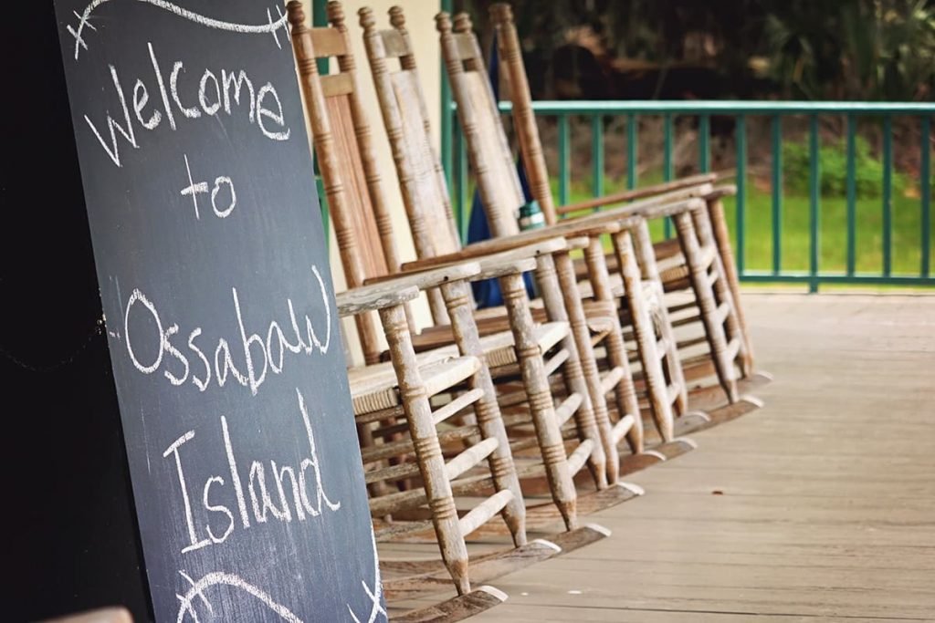 Front porch with rocking chairs and a handwritten sign saying Welcome to Ossabaw Island