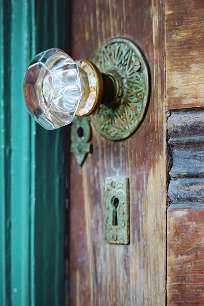 An old wooden door with brass detailing and a glass knob at the entrance to the club house on Ossabaw Island