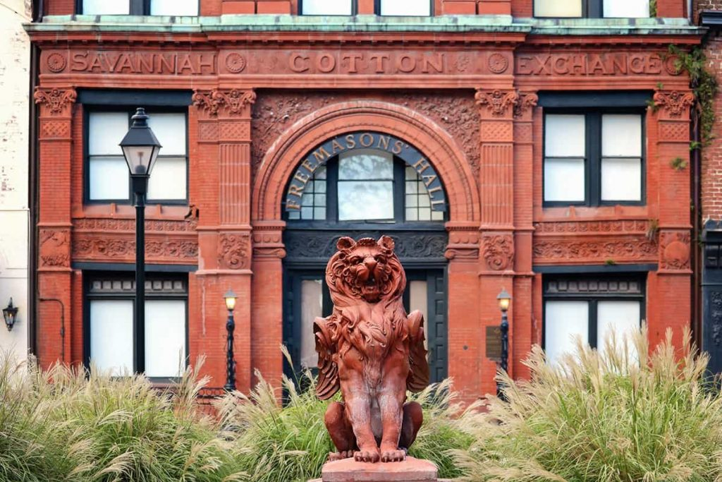 A terra cotta winged lion statue stands guard in front of the Old Savannah Cotton Exchange building