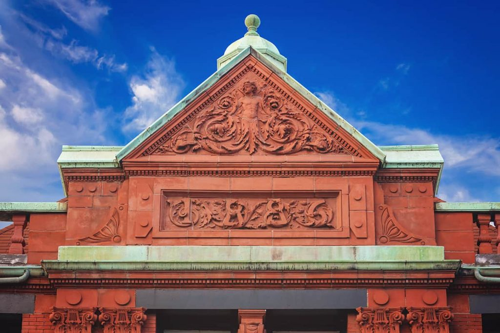 Terra cotta details on the roof of the Old Savannah Cotton Exchange indicate a date of 1886. The copper trim has aged to a soft green patina