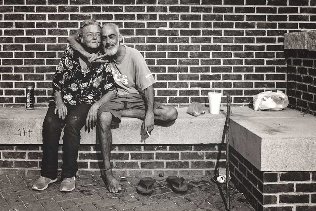B&W photo of a thin, older man homeless man in Savannah with a gray beard and bare feet. His arm is wrapped protectively around the neck of an older female, and he's throwing a peace sign.