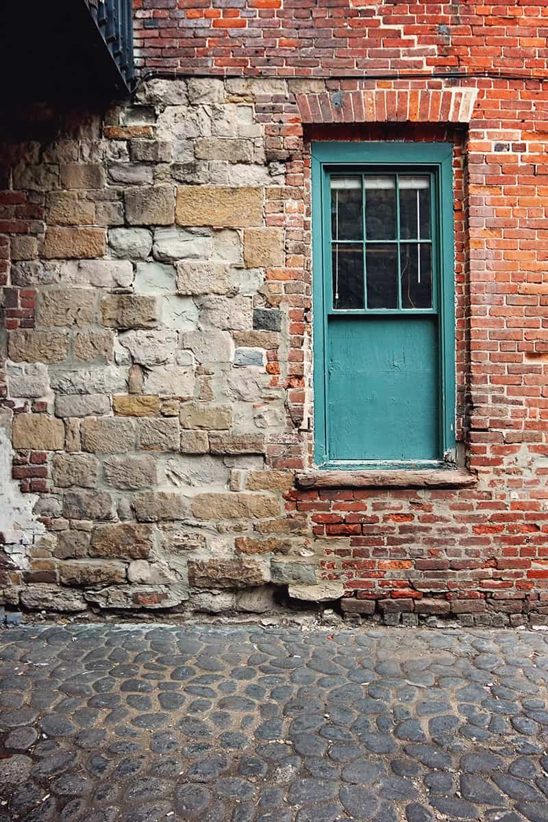 A green-framed window surrounded by a mixture of old bricks and stones along historic Factors Walk