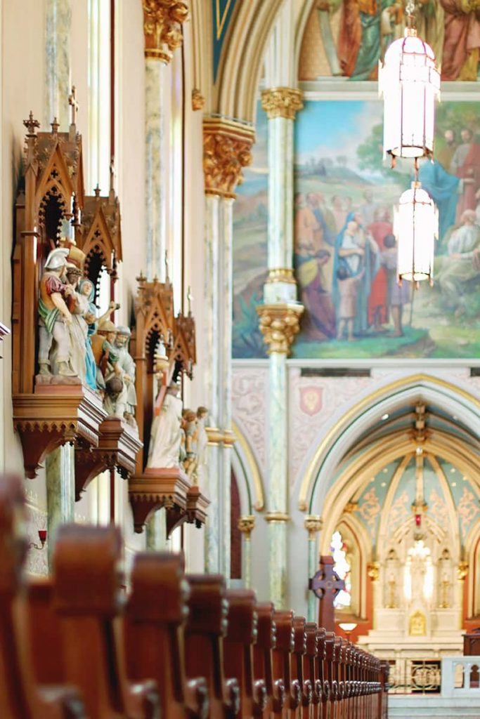 Elaborately carved Stations of the Cross hang on a wall above the pews at the Cathedral Basilica of St. John the Baptist in Savannah, GA