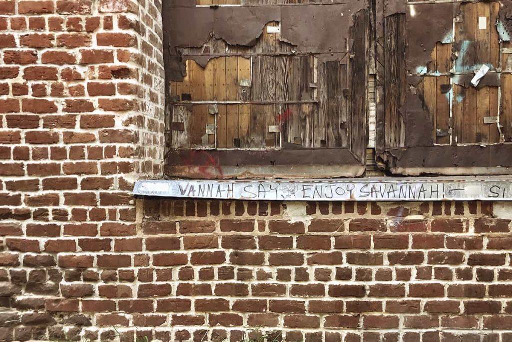Graffiti painted beneath a boarded window on Factors Walk that says Vannah Say, Enjoy Savannah!
