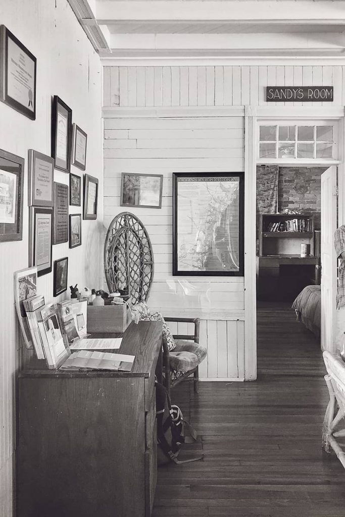 """Room with wood floors, shiplap walls, and a green sign with the words """"Sandy's Room"""" hung over a door frame"""