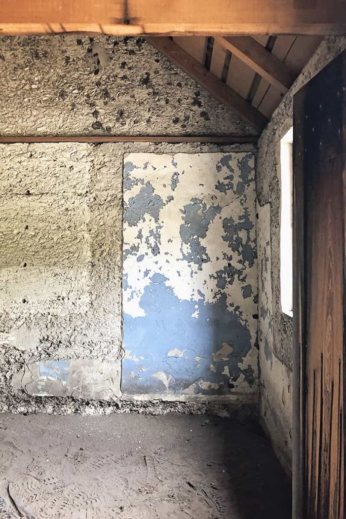 Interior of a slave cabin showing faded and peeling blue paint and walls made of tabby