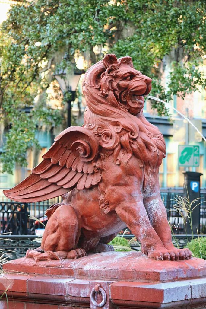 Side view of a terra cotta winged lion statue with a stream of water spraying from its mouth