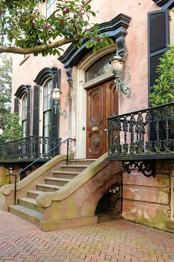 Elaborate front entry in the Savannah Historic District with carved wooden doors, gas lanterns on each side, and historic brick sidewalks