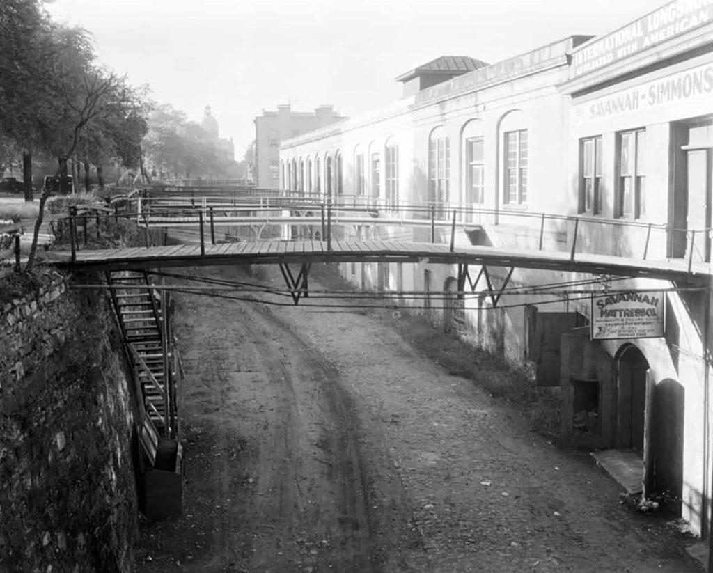 Historic B&W photo of Factors Walk with dirt roads under pedestrian foot bridges along a row of warehouses