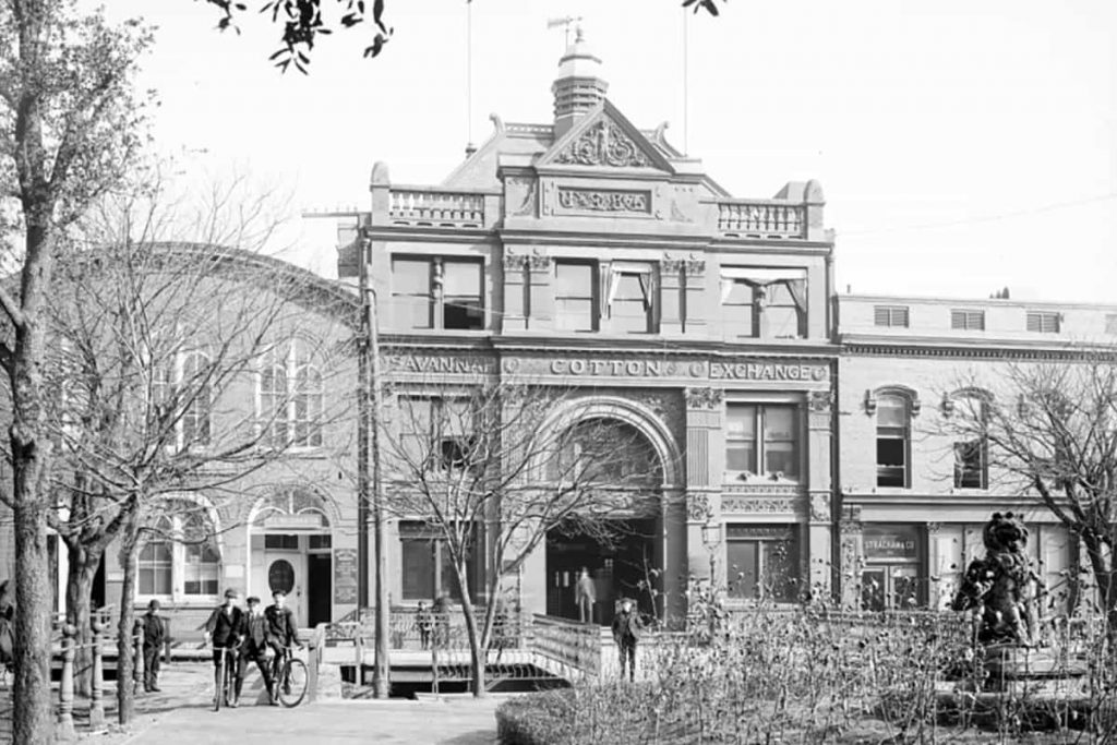 Historic B&W photo of the exterior of the Old Savannah Cotton Exchange building circa 1904 with men in suits and hats standing out front on Factors Walk