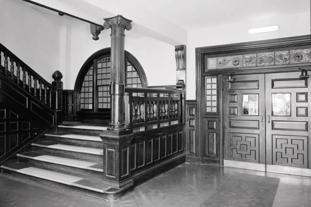 A wide stairwell and oversized doors with stained glass above in the interior of the old Savannah Cotton Exchange building on Factors Walk