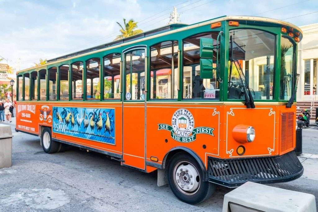 An orange and green trolley with an Old Town Trolley Tours logo on the side