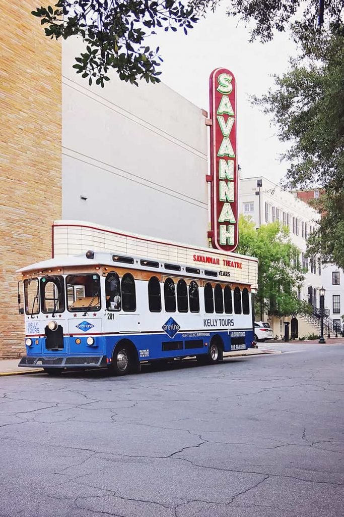 Blue and white Kelly Tours trolley parked in front of the Savannah Theatre marquis sign