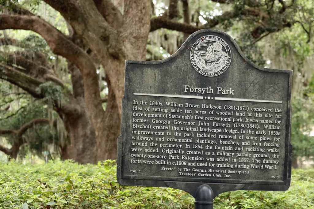 Historic marker for Forsyth Park with beautiful old oak trees in the background