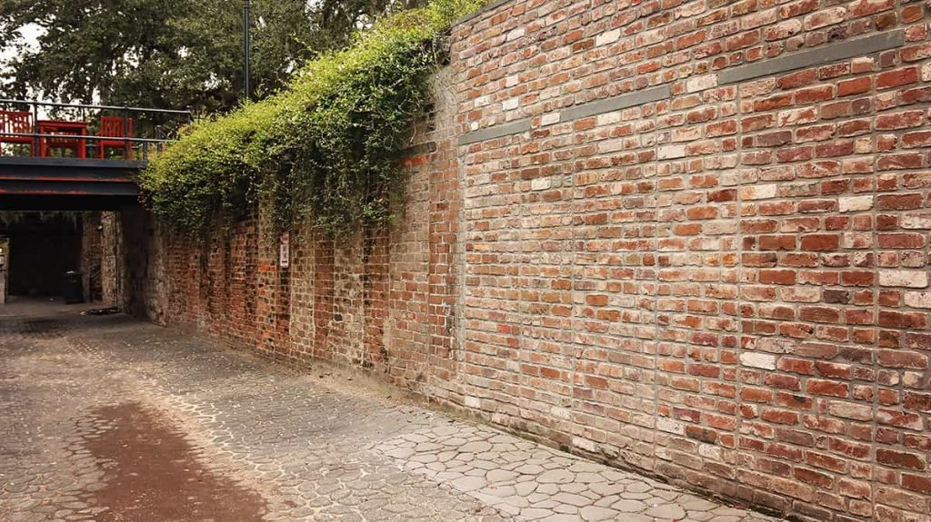 An old brick retaining wall along Factors Walk with clear remnants of tunnels that have been bricked over