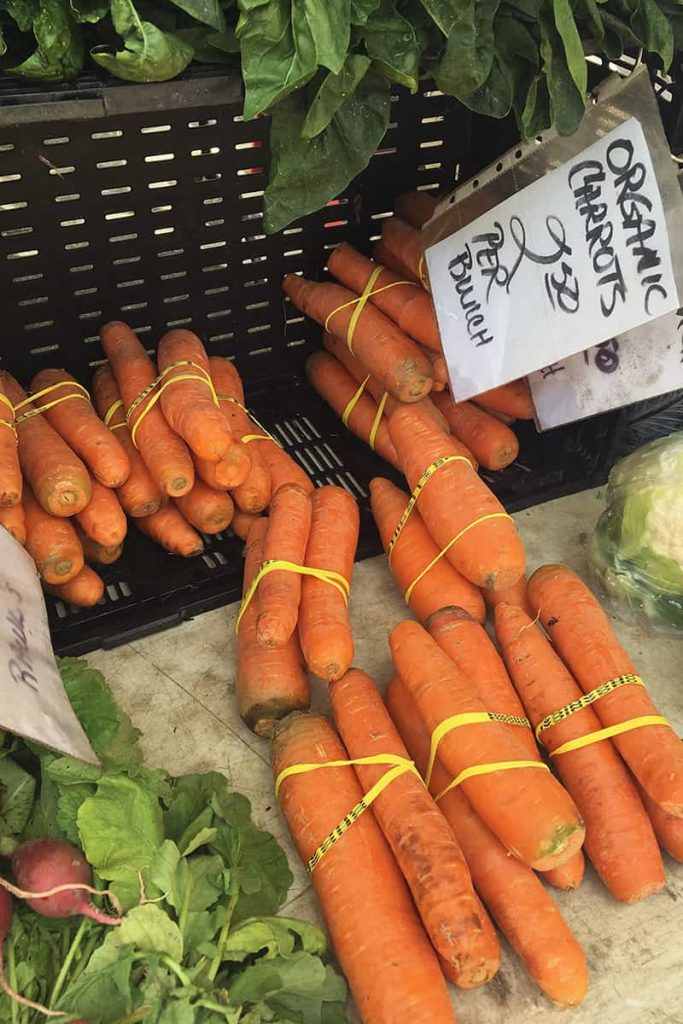 Bundles of carrots in a basket with a hand written sign reading Organic Carrots