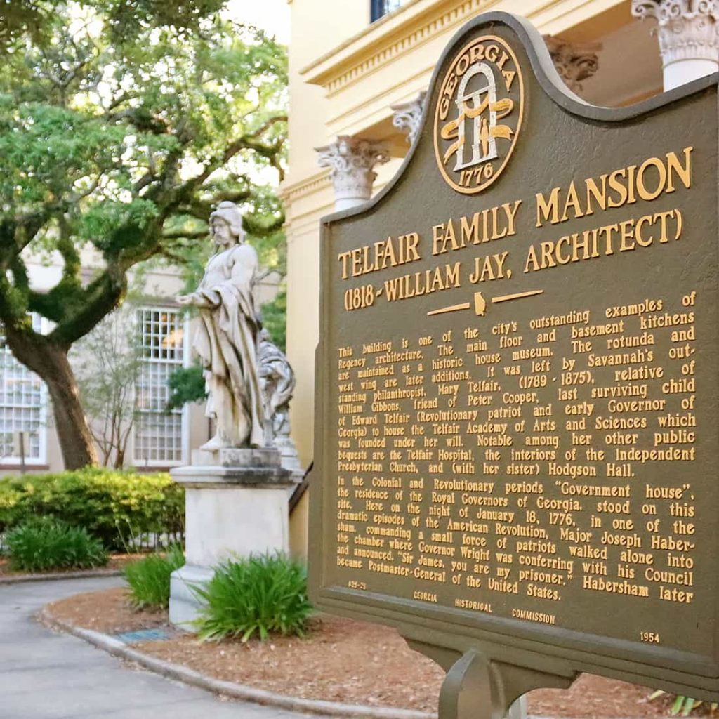 The black and yellow historic marker for the Telfair Family Mansion built by architect William Jay with statues seen behind it in front of Telfair Academy