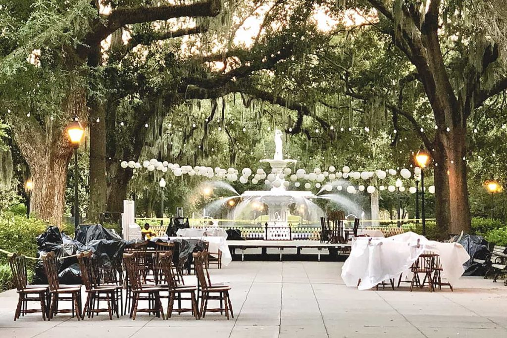 The fountain at Forsyth Park with string lights set up above it and tables and chairs surrounding it, as if for an event