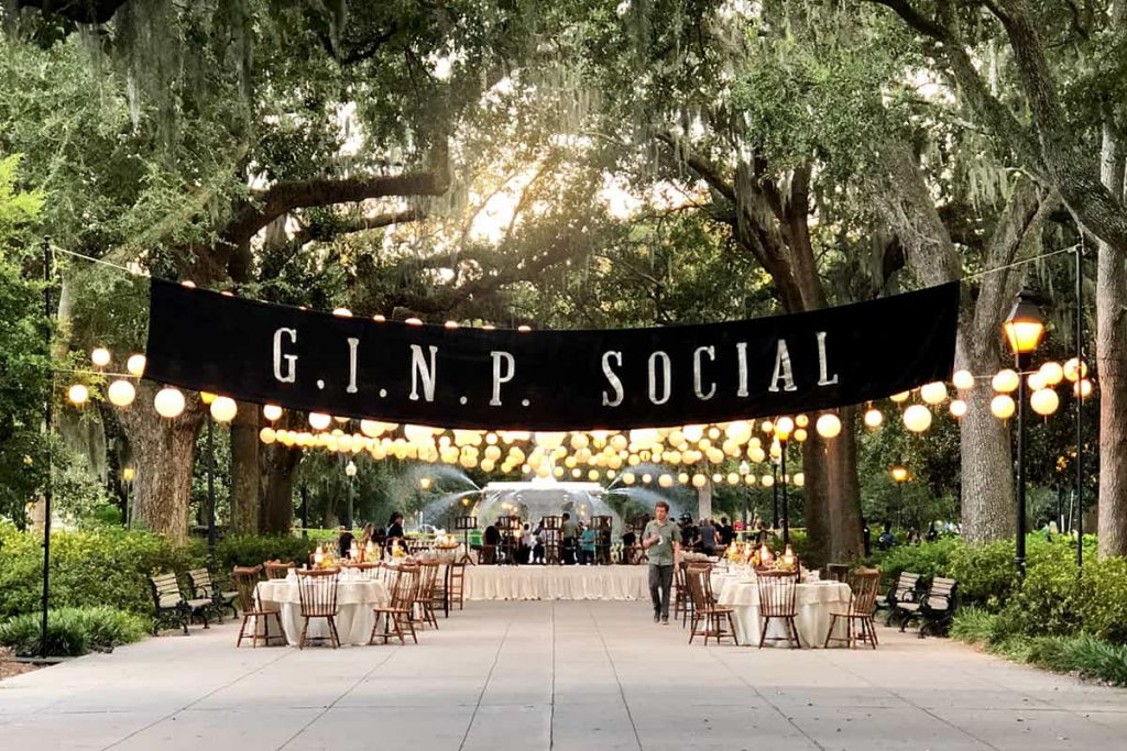 A banner that reads G.I.N.P. Social hangs above a reception area set up in front of the Forsyth Park fountain