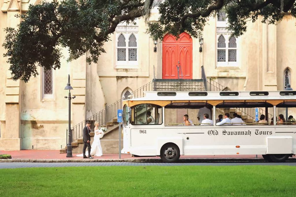 A white trolley with Old Savannah Tours written on its side is parked in front of an old church with red doors and a newly wedded bride and groom walk towards the trolley