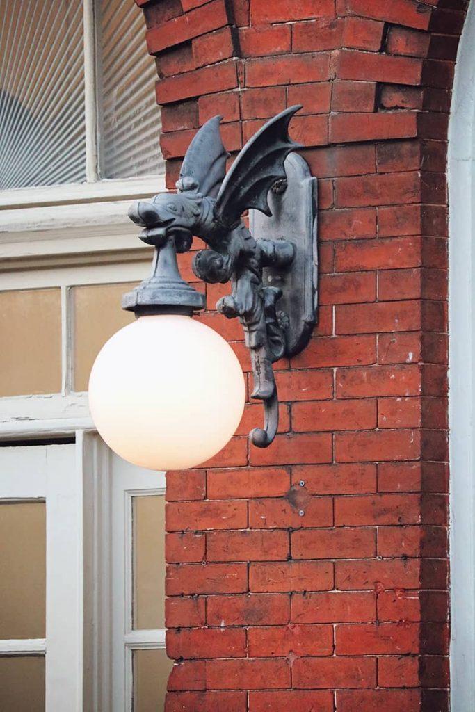 A gargoyle light fixture hangs from beside an arched brick door along Factors Walk