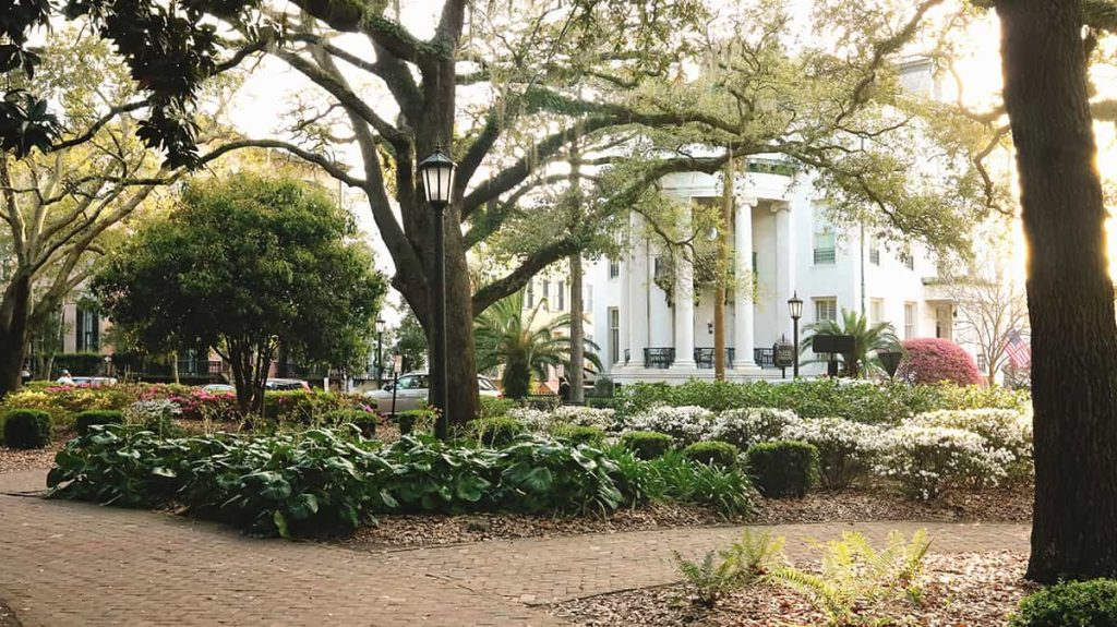 Beautifully manicured Chippewa Square in the foreground with a large white mansion that has a rounded porch with massive columns in the background