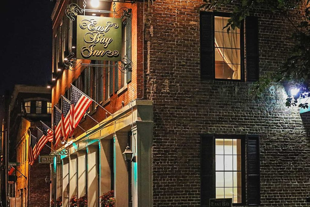 Brick building facade with black shuttered windows and American flags hanging over the front entrance. Sign above the entrance reads East Bay Inn