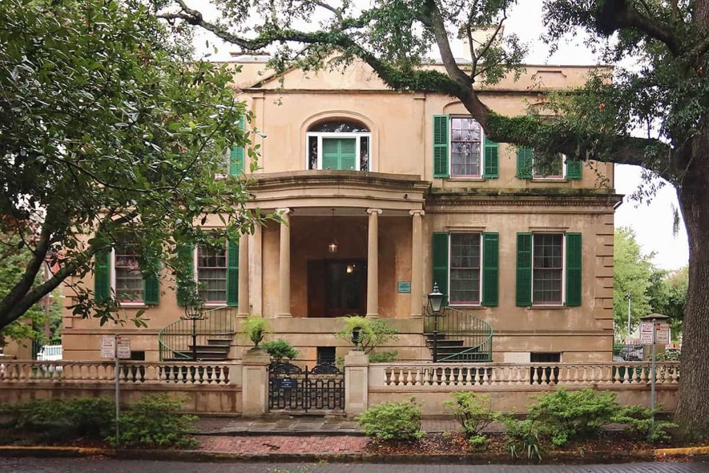 The Owens-Thomas House is an old tan stucco two-story home with green shutters and an elaborate front entry