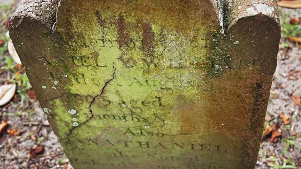 A worn and cracked headstone from the early 1800s covered in moss in Colonial Park Cemetery