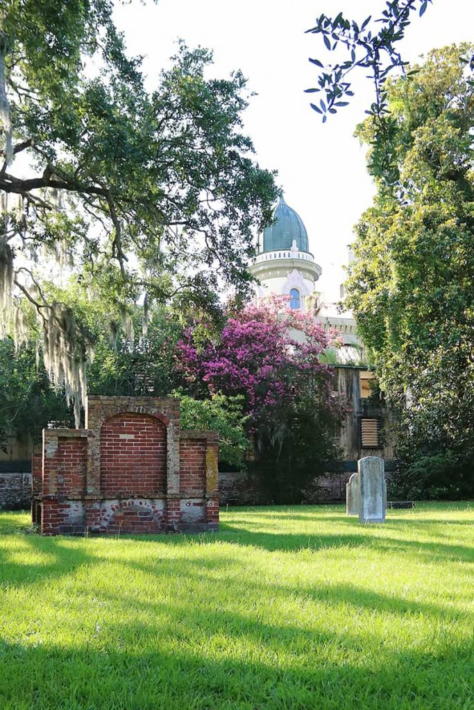 Old headstones and Spanish moss dangling from oak trees in Colonial Park Cemetery with the roofline of a unique building in the background