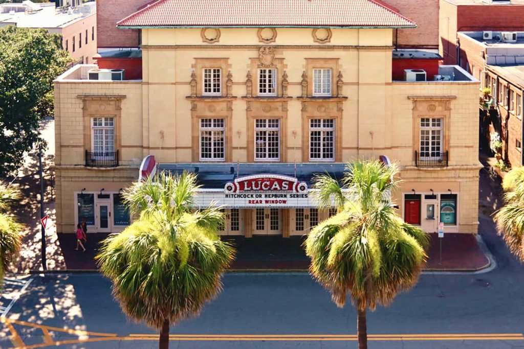 Sand-colored stucco facade of the Lucas Theatre with a red marquis sign and palm trees in front of the building