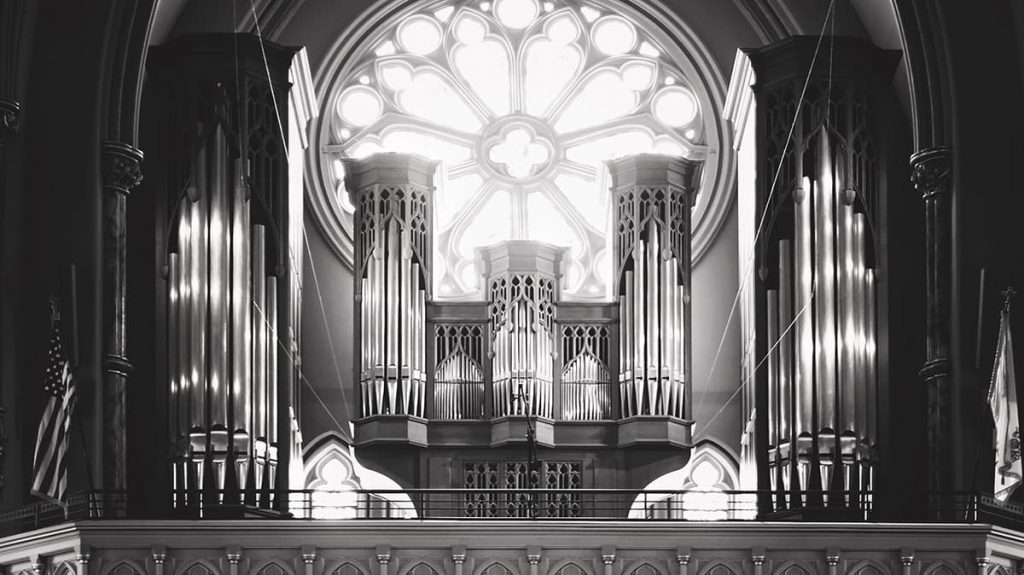 Organ loft in the Cathedral of St. John the Baptist with a large round glass window behind it