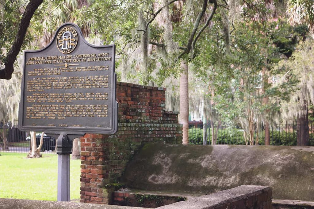 Historic marker for Nathanael Greene in Colonial Park Cemetery with an old brick tomb behind it