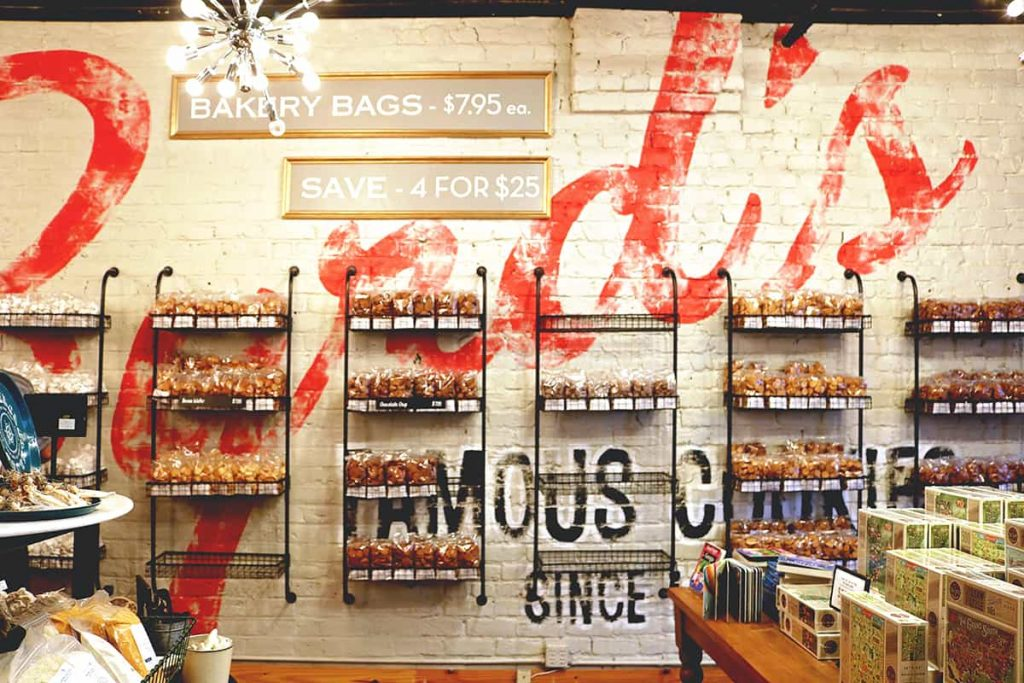 White-painted brick wall with the Byrd's Cookie Co logo painted in red and shelves filled with cookies along the wall