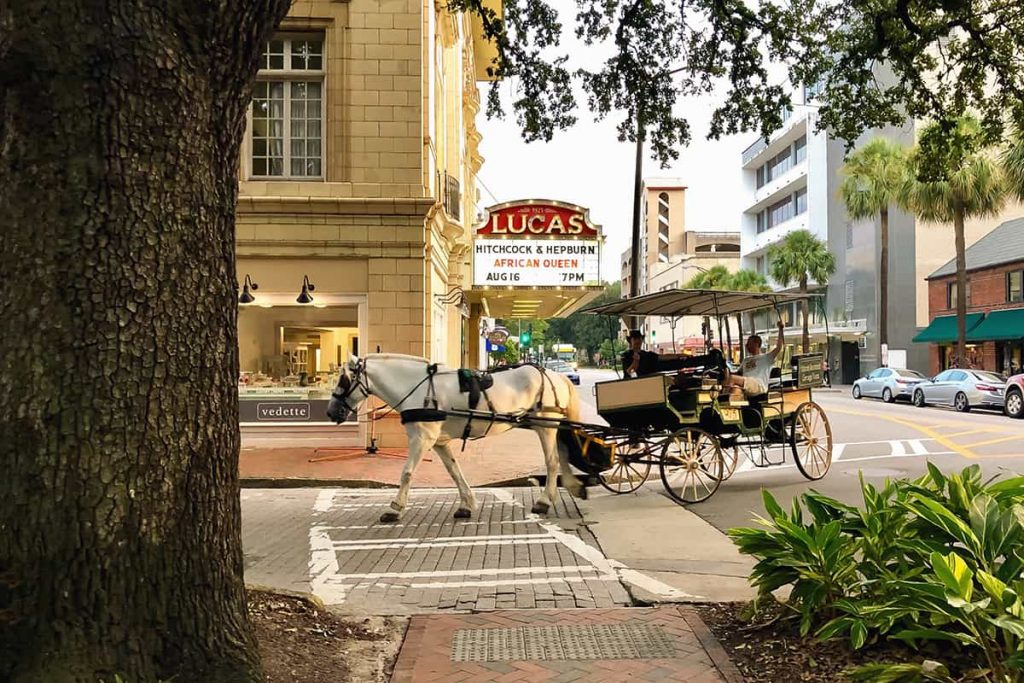 A white horse and carriage pass by the marquis lights of the Lucas Theatre sign