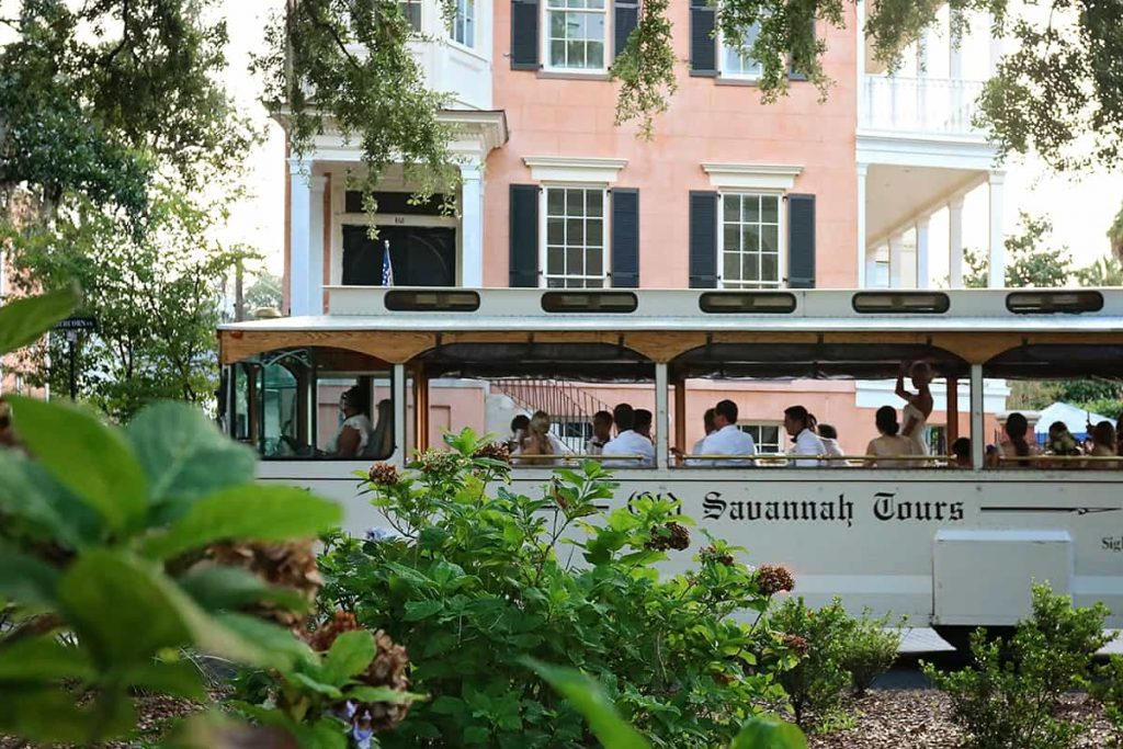 A white Old Savannah Tours trolley in front of a salmon-colored mansion at 432 Abercorn Street in Savannah