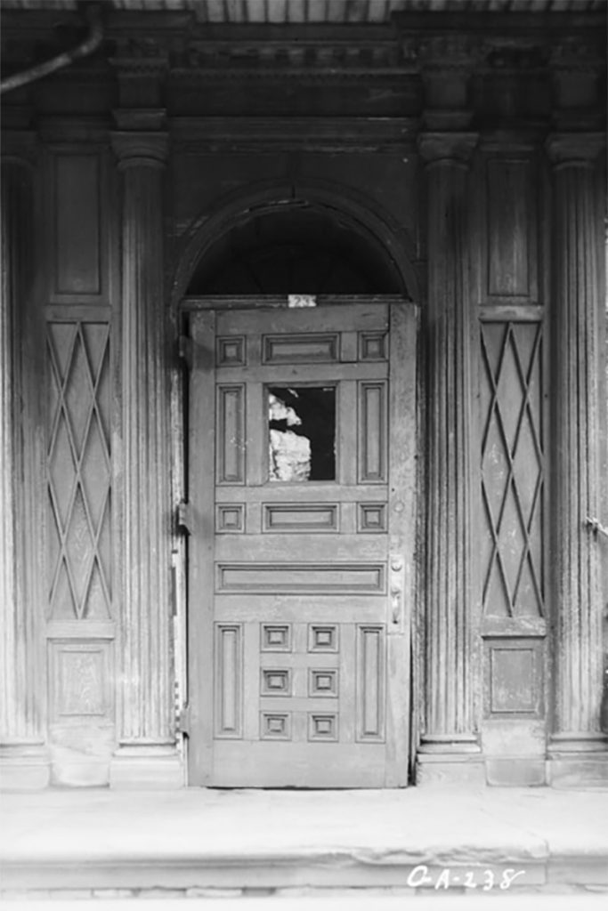 B&W image of a wooden front door and surrounding wood columns at The Olde Pink House, a haunted restaurant in Savannah