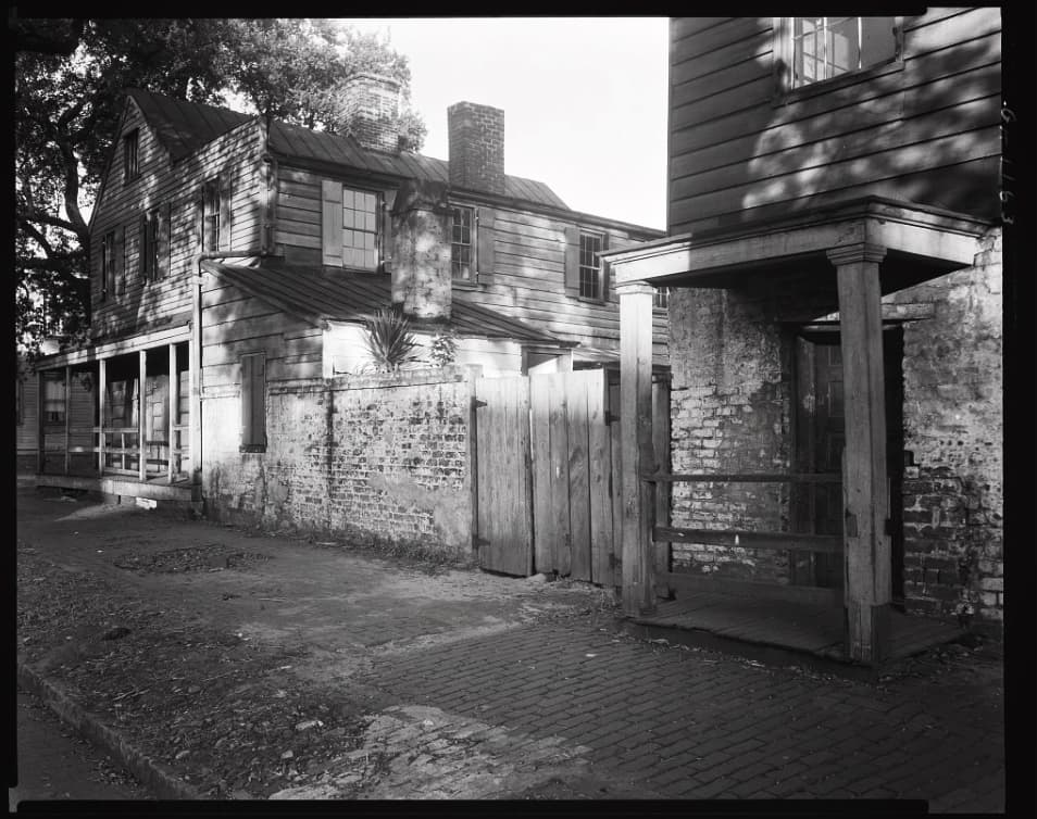 B&W historic photo of The Pirates' House building in Savannah with a structure made from a mixture of whitewashed bricks and wood
