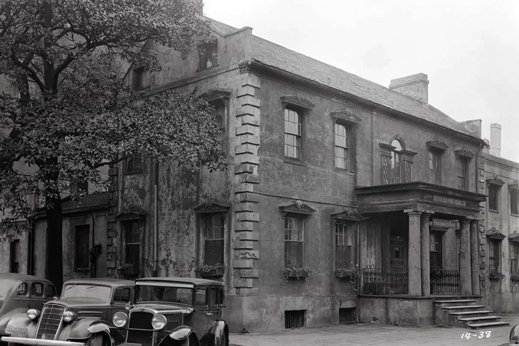 East and south-facing facades of The Olde Pink House, one of the most haunted restaurants in Savannah, in a historic photo from the 1930s with three old-timey cars parked in the foreground