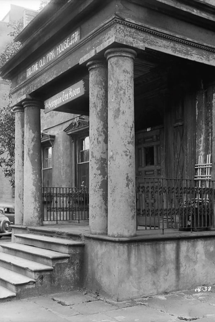B&W photo of the run-down portico of The Olde Pink House when it was operating as the Georgian Tea Room. Old-timey cars can be seen in the background