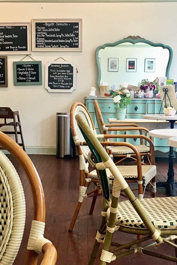 Wicker chairs and a beautiful mint green colored dresser with teas on the top at Cafe M in Savannah