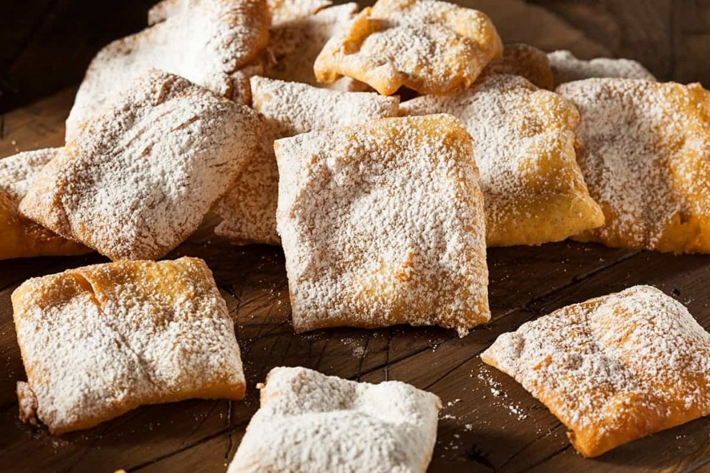 Wooden table piled high with light and flaky beignets dusted in powdered sugar