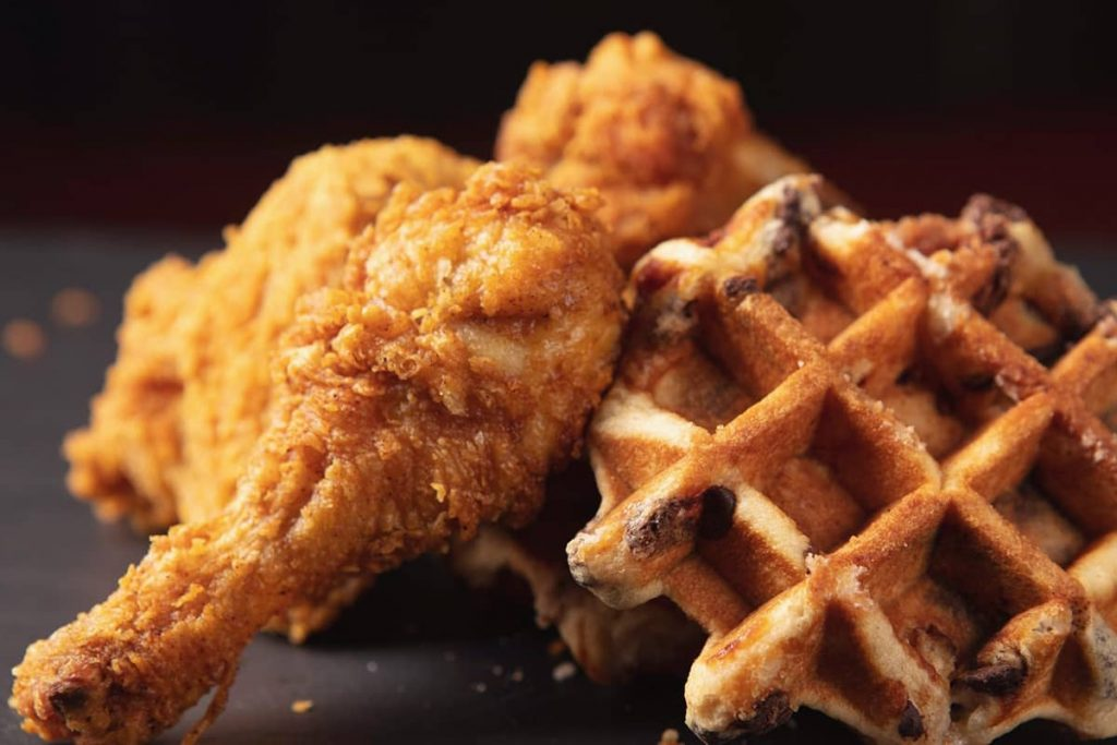Perfectly crisp, lightly fried chicken legs next to a blueberry waffle on a dark plate background