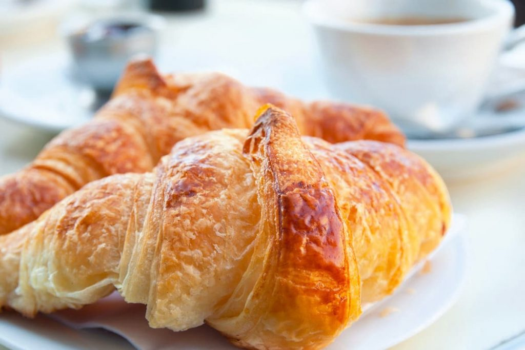 White plate with two flaky, buttery light brown croissants and a white coffee cup in the background