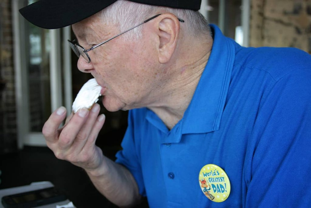 An older gentleman in a blue shirt and black ballcap with a World's Greatest Dad pin on his shirt tastes a beignet at Huey's in Savannah