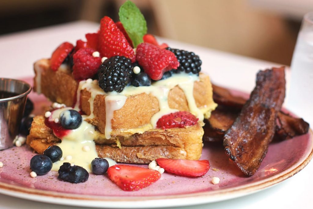 Close up of a pink plate with two pieces of french toast covered in various colorful berries and sweet cream, with a side of bacon at The Collins Quarter in Savannah