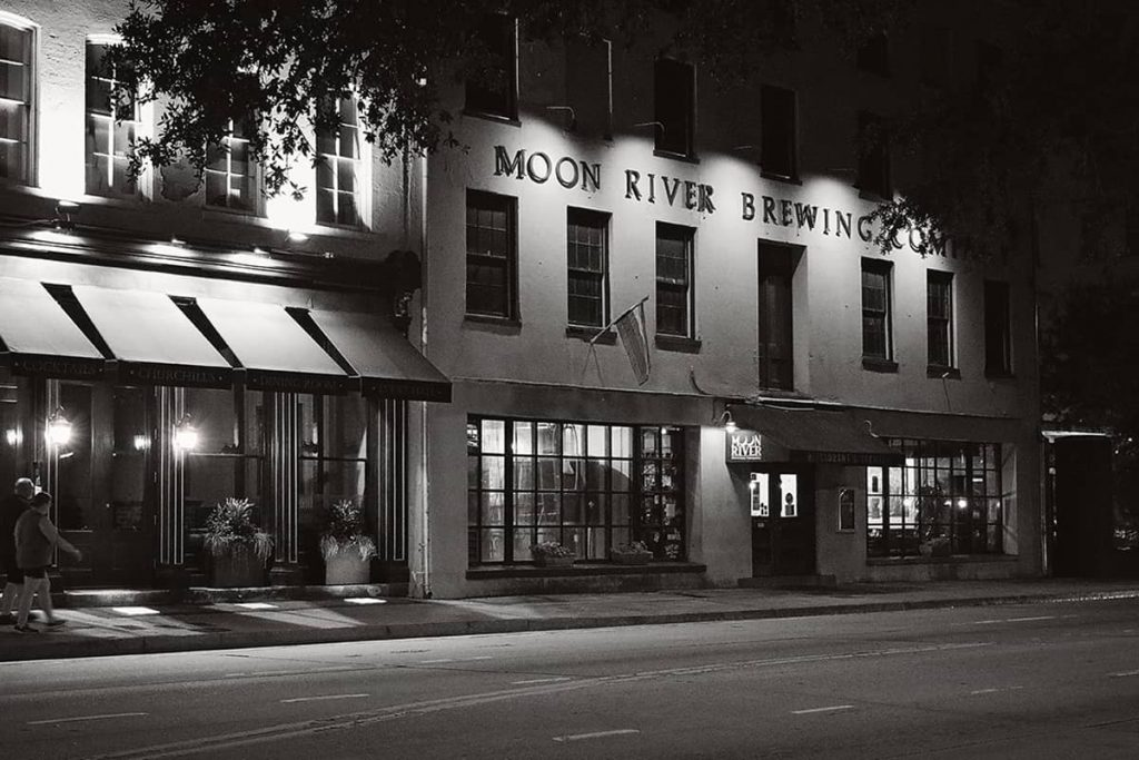 View through some trees at night at a four-story building labeled Moon River Brewing