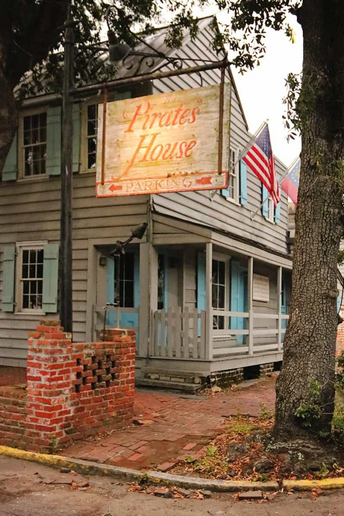 Signage that reads Pirates' House Parking and an old grey wooden inn with haint blue shutters and American flags