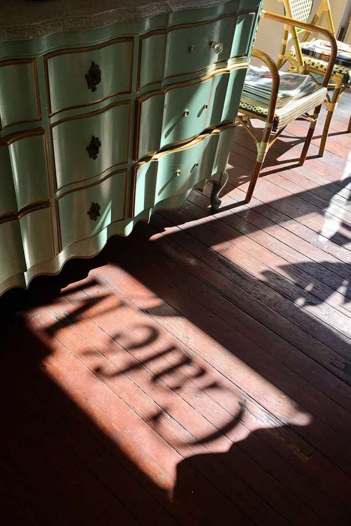 Sunlight streaming through a window causing a silhouetted shadow of the Café M sign in Savannah